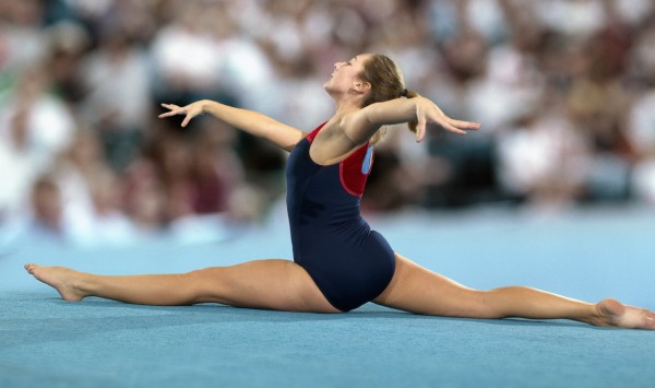 Female gymnast performing her floor exercise doing the splits in front of a large crowd